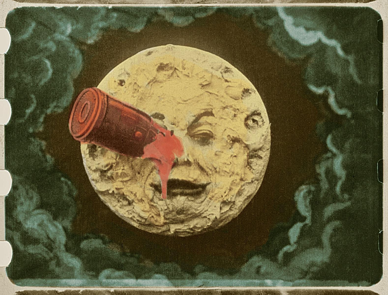 Image of a moon with a face & a red rocket in its eye